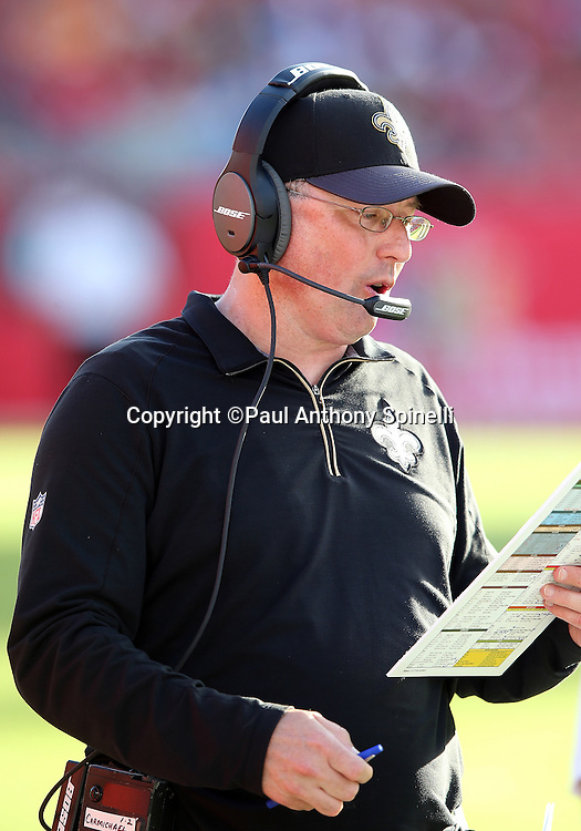 New Orleans Saints offensive coordinator Pete Carmichael looks at his play chart as he calls a play from the sideline during the 2015 week 14 regular season NFL football game against the Tampa Bay Buccaneers on Sunday, Dec. 13, 2015 in Tampa, Fla. The Saints won the game 24-17. (©Paul Anthony Spinelli)