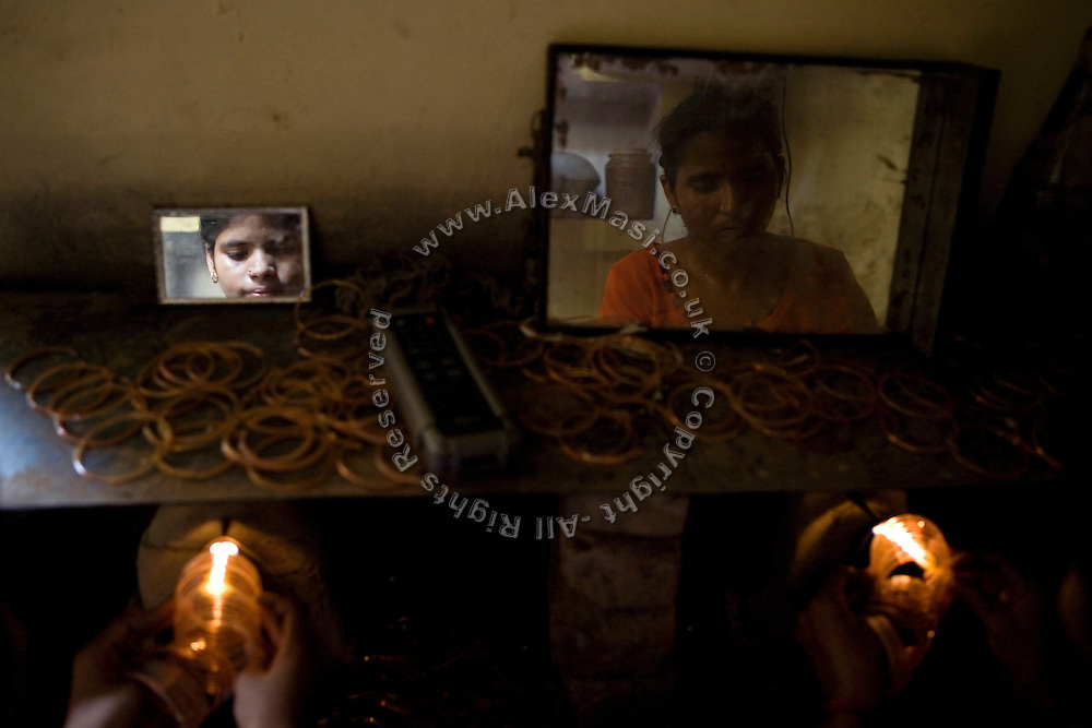 A mother (right) and her young daughter (left) are joining bracelets with the use of a gas flame inside their home, transformed into a small-scale workshop, in the slum surrounding Firozabad, renowned as the 'glass city', in Uttar Pradesh, northern India. Due to extreme poverty, over 20.000 young children are employed to complete the bracelets produced in the industrial units. This area is considered to be one of the highest concentrations of child labour on the planet. Forced to work to support their disadvantaged families, children as young as five are paid between 30-40 Indian Rupees (approx. 0.50 EUR) for eight or more hours of work daily. Most of these children are not able to receive an education and are easily prey of the labour-poverty cycle which has already enslaved their families to a life of exploitation. Children have to sit in crouched positions, use solvents, glues, kerosene and various other dangerous materials while breathing toxic fumes and spending most time of the day in dark, harmful environments. As for India's Child Labour Act of 1986, children under 14 are banned from working in industries deemed 'hazardous' but the rules are widely flouted, and prosecutions, when they happen at all, get bogged down in courts for lengthy periods. A ban on child labour without creating alternative opportunities for the local population is the central problem to the Indian Government's approach to the social issue affecting over 50 million children nationwide.