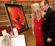 "Debra Murphy, from Centerville and Ron Roddy, from Beavercreek look at items to be auctioned at the 2007 Wellness Connection Red Dress Gala, at the Schuster Performing Arts Center in Dayton, Saturday night, May 5th.  Seen here is a 36"" x 36"" Master Edition of Simon Bull's ""Lady in Red""."