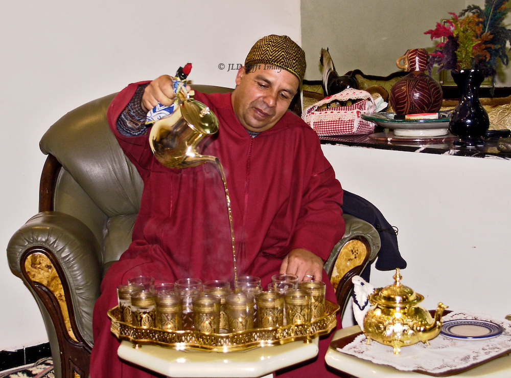 Aziz el Kebir at home with his wife and guests (OAT tour group).  Aziz pours tea, Moroccan style, from a height into tiny glasses.