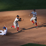 Xander Bogaerts, Boston Red Sox, turns a double play as Michael Conforto, New York Mets, slides into second in the late afternoon sunlight during the New York Mets Vs Boston Red Sox MLB regular season baseball game at Citi Field, Queens, New York. USA. 29th August 2015. Photo Tim Clayton