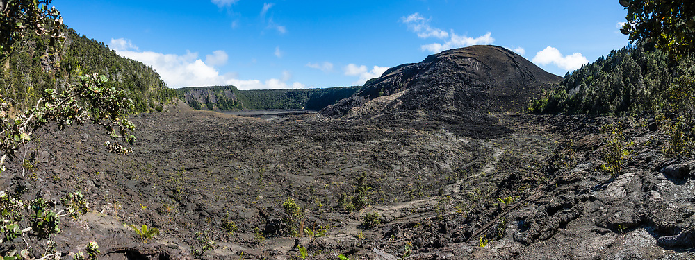 The walkable pit crater of Kilauea Iki (adjacent to the larger caldera of Kilauea) is still warm after last erupting in 1959, in Hawaii Volcanoes National Park, on the Big Island, Hawaii, USA. Established in 1916 and later expanded, the park (HVNP) encompasses two active volcanoes: Kilauea, one of the world's most active volcanoes, and Mauna Loa, the world's most massive shield volcano. HVNP is honored as a UNESCO World Heritage Site and International Biosphere Reserve. This image was stitched from multiple overlapping images.