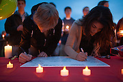 People signing a card at the vigil for slain German exchange student, Diren Dede, on May 2, 2014, at the Fort Missoula soccer field where Dede had played.