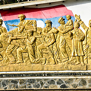 A large gold frieze on the Independence Monument in downtown Sam Neua (also spelled Samneua, Xamneua and Xam Neua) in northeastern Laos. It depicts the Lao struggle for independence, with soldiers, farmers, and workers in gold against the backdrop of the Lao flag.
