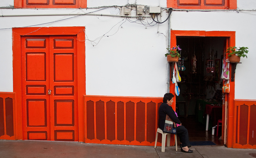 A woman sits outside a store in Salento, Colombia