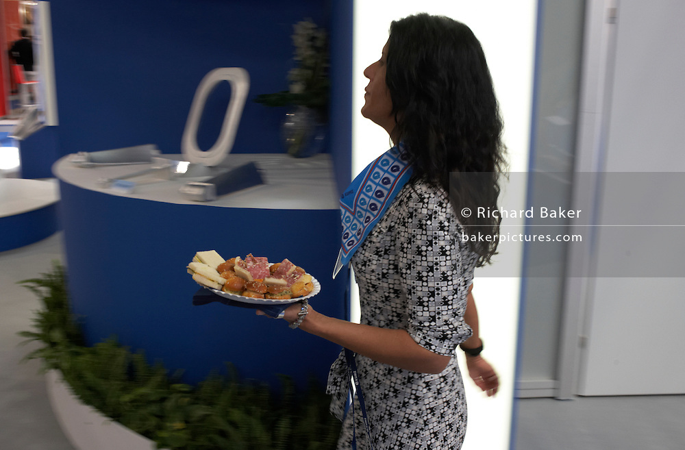 An attractive female employee carries snacks through an exhibition hall during the Paris Air Show  at Le Bourget airfield