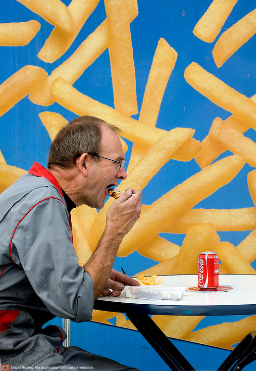 Nederland Rotterdam 5 september 2008 Foto: David Rozing.Man eet friet met frikandel bij frietkot in de europoort..Foto David Rozing