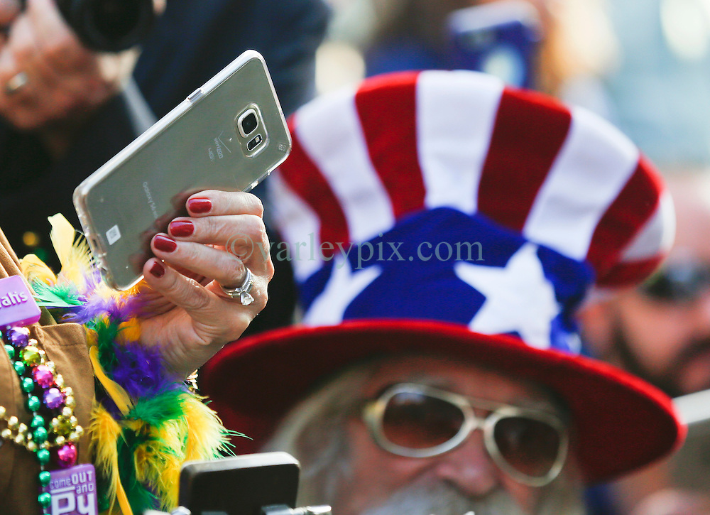 31 January 2016. New Orleans, Louisiana.<br /> Mardi Gras Dog Parade. Bystanders and their mobile phones photograph and video the parade as it winds its way around the French Quarter with dogs and their owners dressed up for this year's theme, 'From the Doghouse to the Whitehouse.' <br /> Photo©; Charlie Varley/varleypix.com