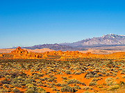 Red rock formations in Valley of Fire State Park, Nevada, USA, with snow-covered mountains in the background. Valley of Fire State Park is located in the Mojave Desert in southern Nevada.