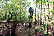 A freeride mountain biker gets airborn over a dirt jump in the woods. (Photo by Bryan Mitchell)