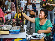 29 NOVEMBER 2015 - BANGKOK, THAILAND:  A vendor in the Amulet Market on Maharat Road on the last day the market was open. Hundreds of vendors used to sell amulets and Buddhist religious paraphernalia to people in the Amulet Market, a popular tourist attraction along Maharat Road north of the Grand Palace near Wat Maharat in Bangkok. Bangkok municipal officials announced that they are closing the market and forcing vendors to relocate to an area about one hour outside of Bangkok. The closing of the amulet market is the latest in a series of municipal efforts to close and evict street vendors and markets from areas that have potential for redevelopment. The street vendors were evicted from the area on Sunday, Nov. 29.      PHOTO BY JACK KURTZ