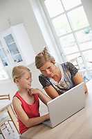 Mother using laptop with daughter at kitchen table