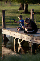 BROTHER AND SISTER SITTING ON A PIER AT A FARM POND FISHING FOR BLUEGILL