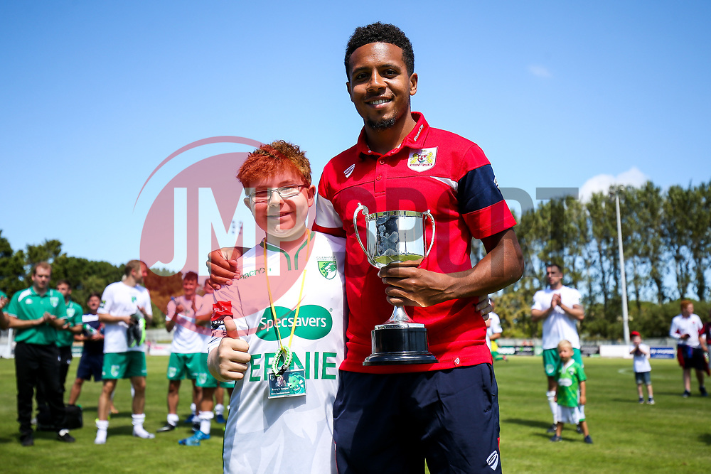Korey Smith of Bristol City is presented with a trophy by the Guernsey mascot after his side win the game 0-1 - Rogan/JMP - 08/07/2017 - Footes Lane - Guernsey - Guernsey FC v Bristol City - Pre-season Friendly.