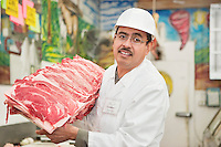Portrait of butcher holding meat tray in store