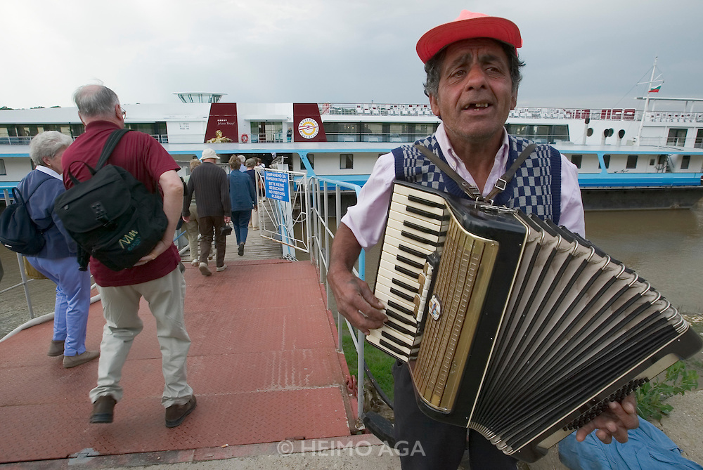 Gipsy musician hoping for coins on the ponton bridge to our boat...M.S. Johann Strauss, a brand new four star+ river cruiser operated by Austrian River Cruises, and chartered by Club 50 (a travel agency especially for seniors aged 50 and up) undertook an epic 3-week journey (May 21 to June 10, 2004) all the way from Amsterdam to the Black Sea?along Rhine, Main and Danube?, presumably the first passenger vessel ever to have done so. This is one of the images recorded during this historic voyage.