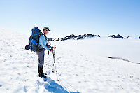 Portrait of a woman on a snow field high above clouds, Mount Rainier National Park, Washington, USA.
