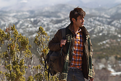 good looking young man walking near the Santa Fe Mountains in New Mexico