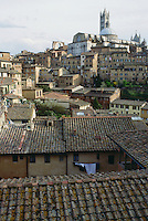 Buildings of Siena and church atop hill Italy