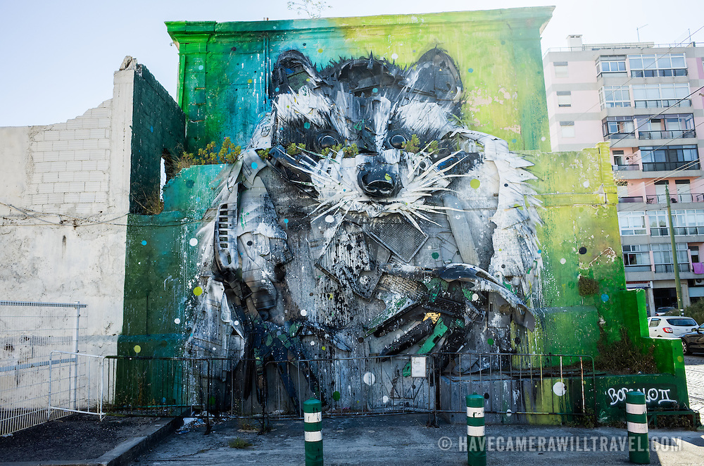 LISBON, Portugal - Part of the Arte Periférica project, this 2015 work of street art on the side of a building in Belem is by Bordalo II and titled Guaxinao or Big Racoon.