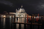 The Basilica di Santa Maria della Salute at night, designed by Baldassare Longhena in Baroque style, built 1631-87, seen from across the Grand Canal with gondola moorings in the foreground, Venice, Italy. The city of Venice is an archipelago of 117 small islands separated by canals and linked by bridges, in the Venetian Lagoon. The historical centre of Venice is listed as a UNESCO World Heritage Site. Picture by Manuel Cohen
