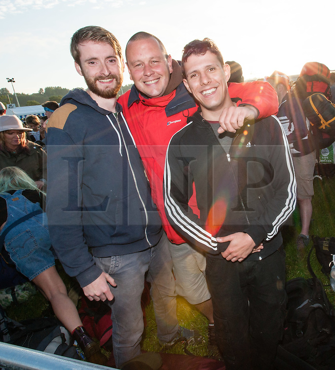 © Licensed to London News Pictures. 24/06/2015. Pilton, UK.   Festival goers arrive at Glastonbury Festival 2015 Wednesday Day 1 of the festival. It is just after dawn and people have been travelling thoughout the night.      These men suffered an breakdown near Bristol and had to make the rest of the journey by taxi. The pedestrian gates to the festival opened at 8am this morning, with many festival goers arriving and waiting throughout last night for the opening.  This years headline acts include Kanye West, The Who and Florence and the Machine, the latter having been upgraded in the bill to replace original headline act Foo Fighters.  Photo credit: Richard Isaac/LNP