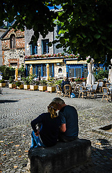 A couple sit in a square near the harbour in Honfleur, Normandy, France