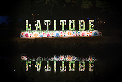 © Licensed to London News Pictures . 22/07/2013 . Suffolk , UK . A large Latitude sign is reflected in the lake . Revellers enjoy the final night of the Latitude Festival . The Latitude music and culture festival in Henham Park , Southwold . Photo credit : Joel Goodman/LNP