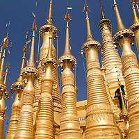 A worker on the Shwe Indein Pagoda gives scale to the mass of golden pagodas found in Indein Village in Inle Lake, Myanmar.
