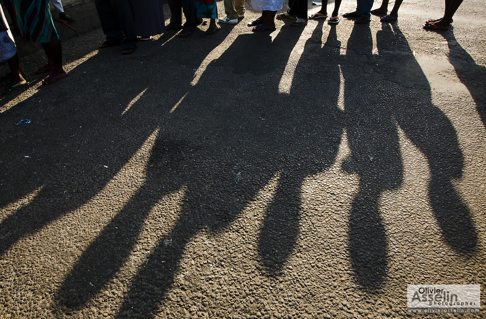 People cast their shadows on the ground as they stand in line at a polling station in Ghana's capital Accra during presidential and parliamentary elections on Sunday December 7, 2008.