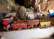Laos, Luang Prabang Province. Pak Ou Buddha caves. Temple offering seller.