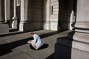 Casually-dressed businessman beneath pillars and columns of Royal Exchange, Cornhill, City of London