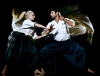 two budokas fighters man and woman practicing Aikido studio shot isolated on black background