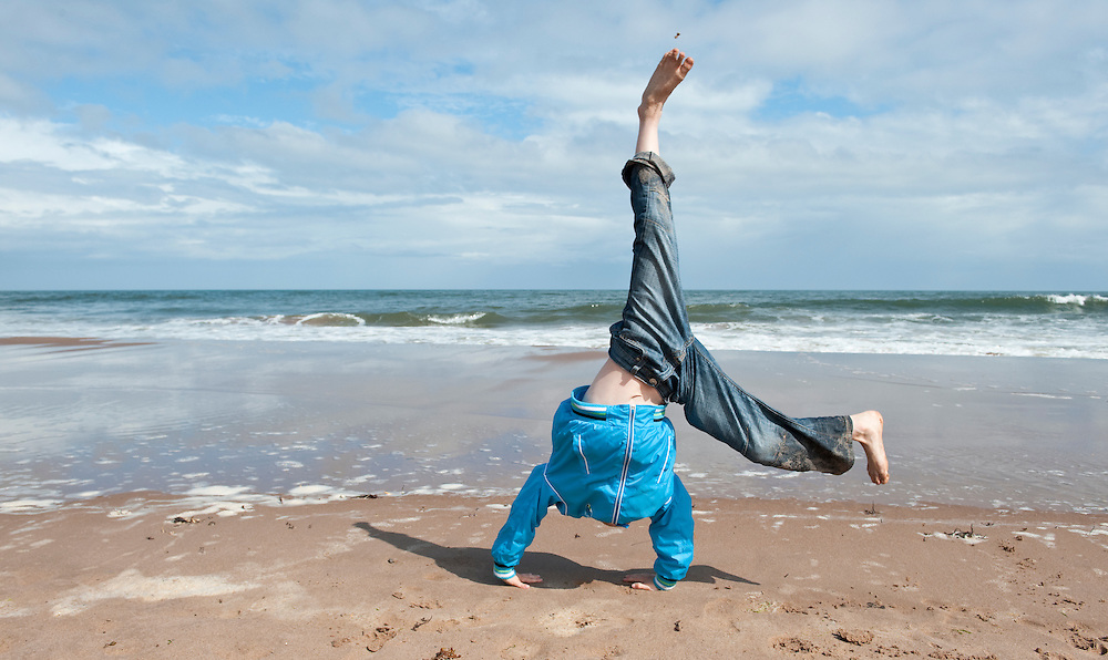 Boy doing a cartwheel on the beach, Scotland