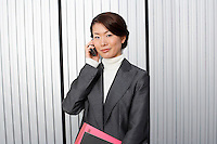 Businesswoman holding paperwork using Cell Phone