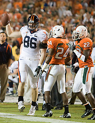 Virginia tight end Tom Santi (86) is pushed out of bounds by Miami (FL) defensive back Chavez Grant (24) and Miami (FL) cornerback Bruce Johnson (22).  The #19 Virginia Cavaliers defeated the Miami Hurricanes 48-0 at the Orange Bowl in Miami, Florida on November 10, 2007.  The game was the final game played in the Orange Bowl.