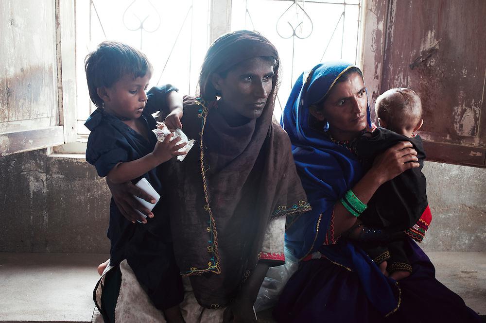 Mothers visit the Tarqwaja Government Dispensary, Thatta, Sindh, Pakistan on June 30, 2011.