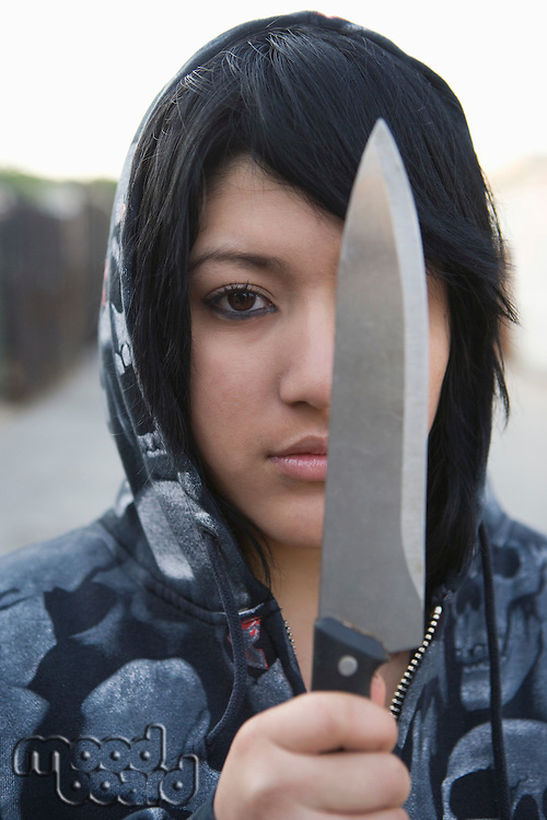 Young woman posing with knife