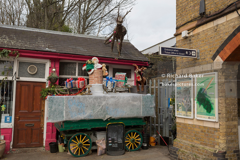 A barrow laden with festive Christmas decorations sits during the closed holiday period (on New Year's Day) outside the florist at Herne Hill Station, on 1st January 2019, in London, England.