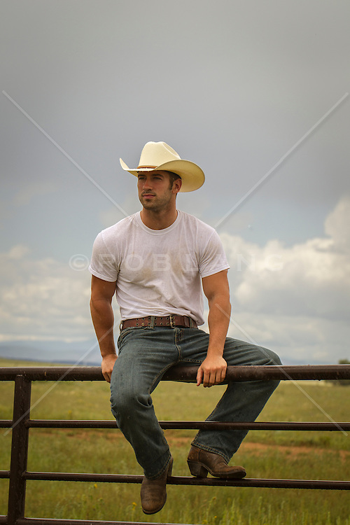 All American cowboy sitting on a fence in New Mexico