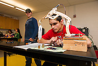 """Justin Padua uses the precision of Michel Tierney's robotic arm to """"Find the Mass"""" during JoAnne Gilbert's Applied Science class at LHS Monday afternoon.  (Karen Bobotas/for the Laconia Daily Sun)"""