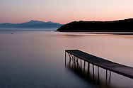 A view of sunrise from Avlaki Beach on Northeast Corfu toward the mountains of Albania.  Corfu, The Ionian Islands, The Greek Islands, Greece, Europe