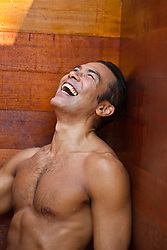 Asian American man in a sauna laughing