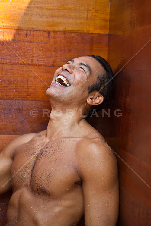 Asian American man in a sauna laughing
