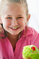 Young girl eating cupcake head and shoulders