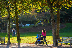 North America, United States, Washington, Bellevue. Young mother pushing a stroller, walking in Downtown Park.