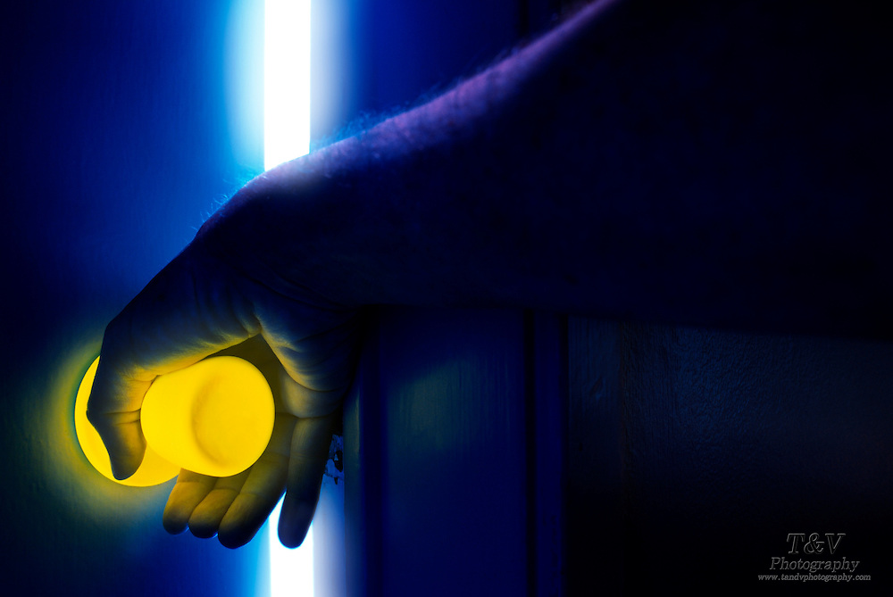 Hand turns glowing door knob and opens door to reveal a white hot space.Black light