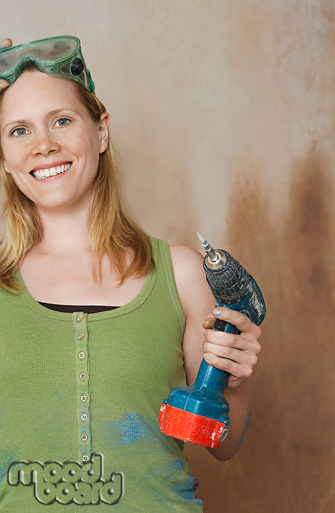 Woman with protective goggles holding power drill portrait