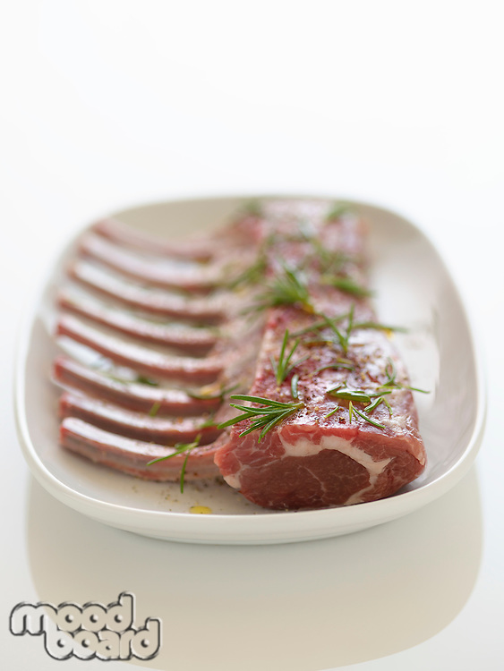 Plate of Fresh raw Ribs with rosemary sprinkled on it