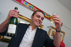 Young man drinking champagne at 18th birthday party UK